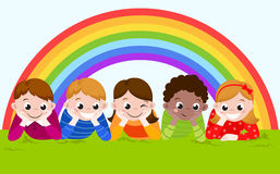 Happy boys and girls lying on a green grass with rainbow. Royalty Free Stock Photography