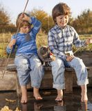 Happy boys go fishing on the river, Two children of the fisher w. Happy boys go fishing on the river , Two children fisher with a fishing rod on the shore of the Stock Photos