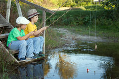 Happy boys go fishing on the river, Two children of the fisher w Royalty Free Stock Photography