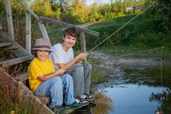 Happy boys go fishing on the river, Two children of the fisherma. N with a fishing rod on the shore of the lake Royalty Free Stock Photo
