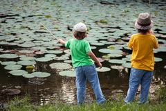 Happy boys go fishing on the river, Two children of the fisherma Royalty Free Stock Photo