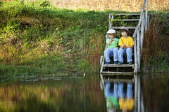 Happy boys go fishing on the river, Two children of the fisherma Royalty Free Stock Photography