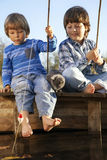 Happy boys go fishing on the river, Two children of the fisherma Stock Photos