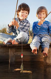Happy boys go fishing on the river, Two children of the fisherman with a fishing rod on the shore of lake royalty free stock photo