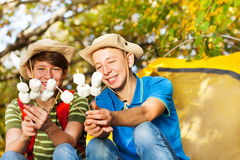 Happy boys with hats hold marshmallow sticks Royalty Free Stock Photos