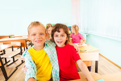 Happy boys hug and sit together in classroom Stock Images