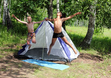 Happy boys jumping near camping tent. In summer forest Royalty Free Stock Photo