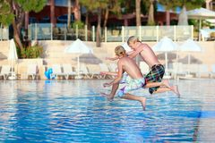 Happy boys jumping in swimming pool. Two happy children, twin brothers are jumping into swimming pool at the resort at sunset Royalty Free Stock Images