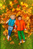 Happy boys laying on the autumn leaves Royalty Free Stock Images