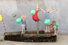 Happy boys play pirates and seafarers. Three brothers have fun together. The old boat is decorated with balloons.  Royalty Free Stock Photo