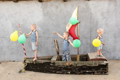 Happy boys play pirates and seafarers. Three brothers have fun together. The old boat is decorated with balloons.  Stock Photos