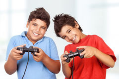 Happy boys playing video games. Portrait of a two cute happy boys playing video games at home, best friends enjoying competition on playstation, with pleasure Royalty Free Stock Photo