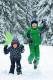 Happy boys playing on a winter walk in nature. Children jumping and having fun in winter park stock images