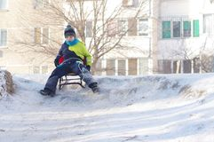 Cute Child sledding. Toddler boy riding a sledge in the snow stock photo