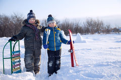 Happy boys on sled and Skis. Two happy boys on sled and Skis in winter outdoors Royalty Free Stock Photo