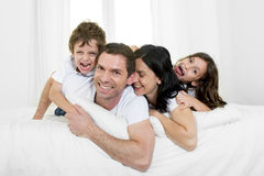 Happy Brazilian family playing together on bed having fun smiling and laughing Stock Photo
