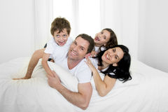 Happy Brazilian family playing together on bed having fun smiling and laughing Stock Images
