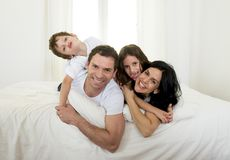 Happy Brazilian family playing together on bed having fun smiling and laughing Stock Photography