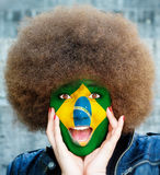 Happy brazilian fan. Portrait of a happy brazilian girl with a painted flag Royalty Free Stock Photography