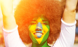 Happy brazilian fan in the sun. Portrait of a happy brazilian girl with a painted flag Royalty Free Stock Image