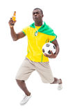 Happy brazilian football fan holding ball and beer. On white background Royalty Free Stock Photo