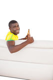 Happy brazilian football fan sitting on couch with a beer Royalty Free Stock Image