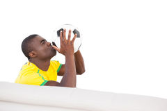 Happy brazilian football fan sitting on couch kissing ball Stock Photos