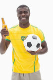 Happy brazilian football fan in yellow holding beer and ball Stock Photography