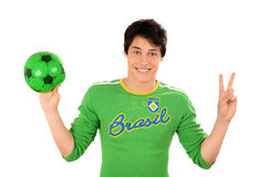 Happy Brazilian man with a football ball in the hands signing victory for Brazil. Royalty Free Stock Photo