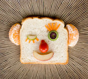 Happy bread face on ceramic plate. Funny happy winking face made with bread, fruit and vegetables Stock Image