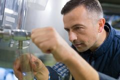 Happy brewer checking beer with hydrometer at brewery stock photo