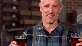 Happy brewery worker holding two pints. In a cellar stock video