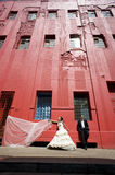 Happy bridal couple standing on sidewalk below tall red building Stock Photo
