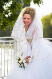 Happy bride. Young bride standing on the bridge in the park Royalty Free Stock Photography