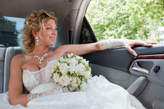 Happy bride. Bride sits in the car and looks out of the window stock images