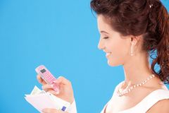 Happy bride. With calculator and money over blue stock images