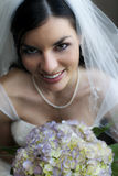 Happy bride. A beautiful smiling bride holding her bouquet royalty free stock photos