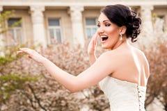 Happy bride. Happy beautiful bride dancing in wedding dress outside stock photography