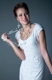 Happy bride. Studio portrait of pretty smiling bride wearing white dress,beautifu makeup and elegant hairdo, lot of jewelry like beads, pearls, earrings, rings Royalty Free Stock Photography