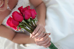 Happy bride. Unique angle of young woman dressed in wedding dress wearing necklace and holding bouquet of red roses smiling, three quarter length Stock Photography