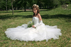 Happy bride. Bride sits on lawn in park Royalty Free Stock Photography