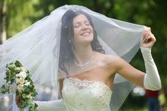 Happy bride. Portrait of beautiful happy bride in wedding wear with bouquet stock images