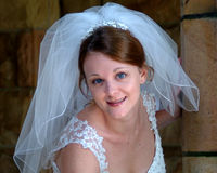 Happy Bride. Closeup of smiling bride in front of stone wall stock photography