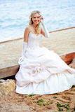 Happy bride. Beautiful happy bride itting on berth at beach and smiling stock photography
