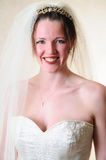Happy Bride. Female model standing in her wedding gown with a very happy smile on her face Stock Image
