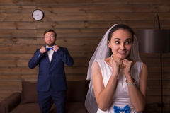 Happy bride against groom talking on the phone Royalty Free Stock Images
