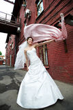 Happy bride on background of old red building Stock Photo