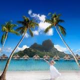 Happy bride on a beach. The happy bride on a beach with palm trees and mountain Otemanu on a background. Bora-Bora. Polynesia stock photos