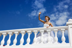 Happy Bride at the Blue Sky. Happy smiling bride standing on the terrace and greeting somebody Royalty Free Stock Image