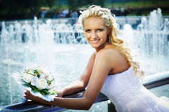 Happy bride with bouquet of flower near fountain Royalty Free Stock Images